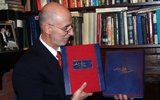 The Publisher, Irvin Ungar, Holds the Deluxe and Premier Editions of the Szyk Haggadah.
